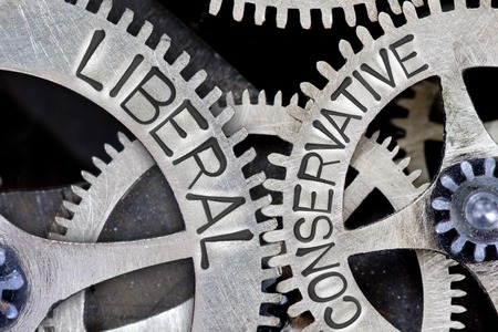 Macro photo of tooth wheel mechanism with imprinted LIBERAL, CONSERVATIVE concept words Stock Photo