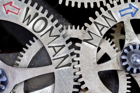 challenging sex: Macro photo of tooth wheel mechanism with imprinted arrows and WOMAN, MAN concept words