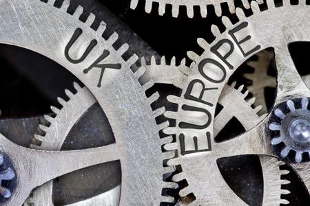 international crisis: Macro photo of tooth wheel mechanism with imprinte UK, EUROPE concept words Stock Photo