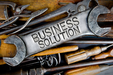 business letters: Photo of various tools and instruments with BUSINESS SOLUTION letters imprinted on a clear wrench surface