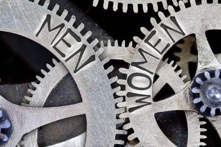 challenging sex: Macro photo of tooth wheel mechanism with imprinted MEN, WOMEN concept words