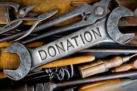 generosity: Foto de diversas herramientas e instrumentos con letras impresas DONACIÓN sobre una superficie clara llave