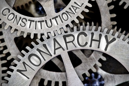 constitutional: Macro photo of tooth wheel mechanism with CONSTITUTIONAL MONARCHY letters imprinted on metal surface Stock Photo