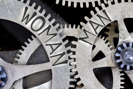 challenging sex: Macro photo of tooth wheel mechanism with imprinted WOMAN, MAN concept words