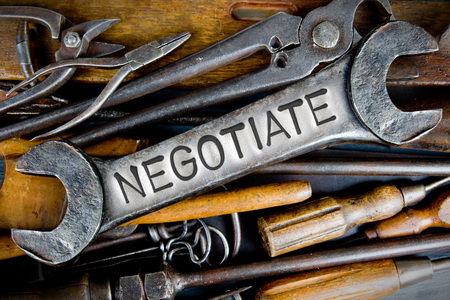 Photo of various tools and instruments with NEGOTIATE letters imprinted on a clear wrench surface