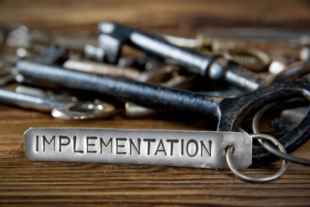 Foto des Schlüsselbündels auf hölzernem Brett und Tag mit den Buchstaben aufgeprägt auf saubere Metalloberfläche; Konzept der UMSETZUNG