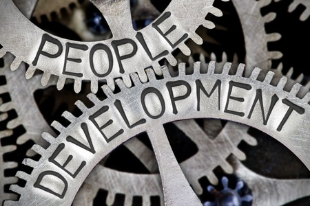 people development: Macro photo of tooth wheel mechanism with PEOPLE DEVELOPMENT letters imprinted on metal surface