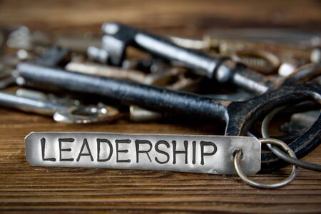 heap of role: Photo of key bunch on wooden board and tag with letters imprinted on clean metal surface; concept of LEADERSHIP