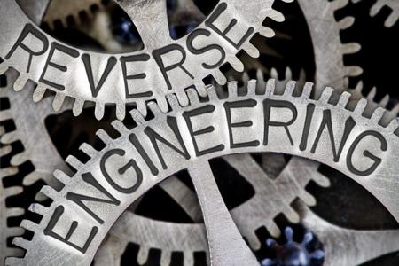 Macro photo of tooth wheel mechanism with REVERSE ENGINEERING letters imprinted on metal surface Reklamní fotografie