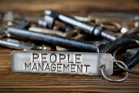 Photo of key bunch on wooden board and tag with letters imprinted on clean metal surface; concept of PEOPLE MANAGEMENT Stock Photo