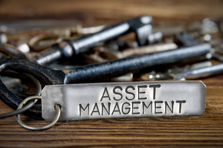 operating key: Photo of key bunch on wooden board and tag with letters imprinted on clean metal surface; concept of ASSET MANAGEMENT Stock Photo