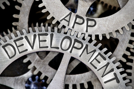os: Macro photo of tooth wheel mechanism with APP DEVELOPMENT concept letters