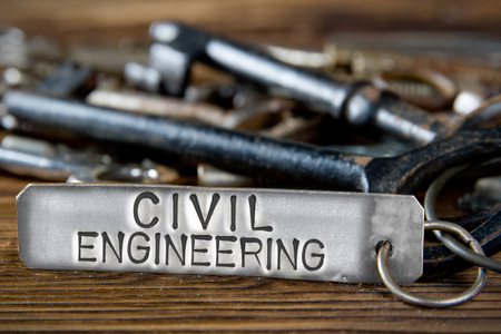 Photo of key bunch on wooden board and tag with letters imprinted on clean metal surface; concept of CIVIL ENGINEERING Stock Photo