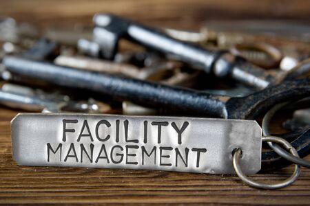 Photo of key bunch on wooden board and tag with letters imprinted on clean metal surface; concept of FACILITY MANAGEMENT