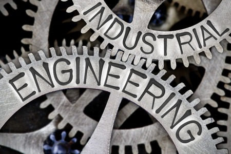 industrial machinery: Macro photo of tooth wheel mechanism with INDUSTRIAL ENGINEERING letters imprinted on metal surface Stock Photo