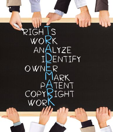 ownership and control: Photo of business hands holding blackboard and writing TRADEMARK concept