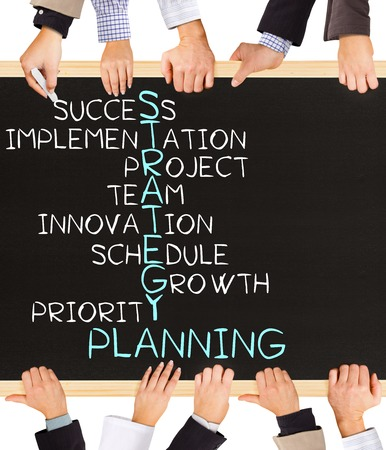 Photo of business hands holding blackboard and writing STRATEGY PLANNING concept
