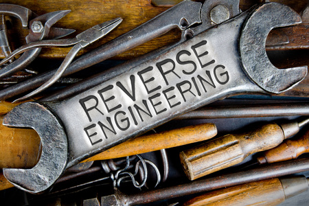 reproducing: Photo of various tools and instruments with REVERSE ENGINEERING letters imprinted on a clear wrench surface Stock Photo