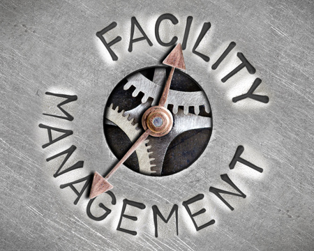 property management: Macro photo of pointer and tooth wheel mechanism with FACILITY MANAGEMENT letters imprinted on metal surface Stock Photo