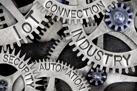 Foto macro di ruote dentate con parole INDUSTRY, IoT, CONNECTION, AUTOMATION e SECURITY impresse su una superficie metallica