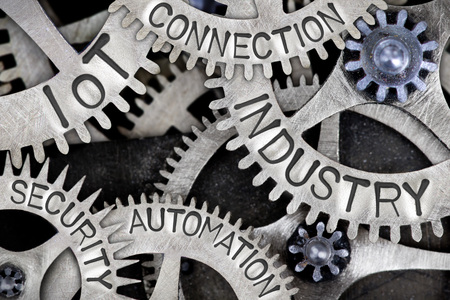 Macro photo of tooth wheels with INDUSTRY, IoT, CONNECTION, AUTOMATION and SECURITY words imprinted on metal surface
