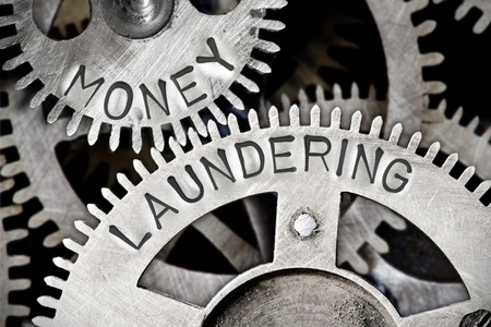 Macro photo of tooth wheel mechanism with MONEY LAUNDERING letters imprinted on metal surface 스톡 콘텐츠