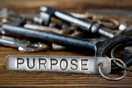 heap of role: Photo of key bunch on wooden board and tag with letters imprinted on clean metal surface; concept of PURPOSE Stock Photo