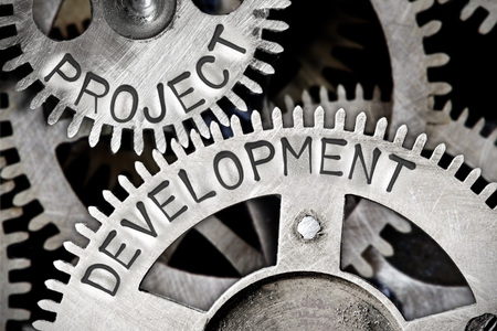 advice: Macro photo of tooth wheel mechanism with PROJECT DEVELOPMENT concept letters Stock Photo