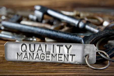 Photo of key bunch on wooden board and tag with letters imprinted on clean metal surface; concept of QUALITY MANAGEMENT
