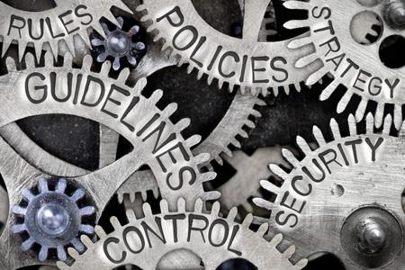 Zdjęcie makro mechanizmu z kołem zębatym ze słowami koncepcyjnymi WYTYCZNE, KONTROLA, POLITYKI, BEZPIECZEŃSTWO, STRATEGIA i ZASADY Zdjęcie Seryjne