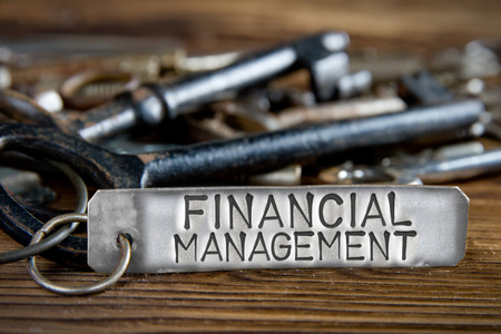 Photo of key bunch on wooden board and tag with letters imprinted on clean metal surface; concept of FINANCIAL MANAGEMENT Stock Photo