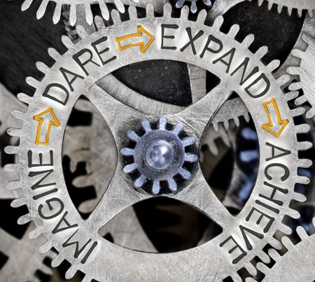 Macro photo of tooth wheel mechanism with IMAGINE, DARE, EXPAND and ACHIEVE words imprinted on metal surface