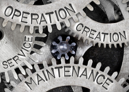 Macro photo of tooth wheel mechanism with CREATION, OPERATION, MAINTENANCE, SERVICE concept words imprinted on metal surface Stock fotó