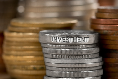 Photo of various stacks and rows of coins with INVESTMENT concept word imprinted on metal surface