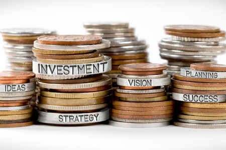 Photo of various stacks and rows of coins isolated on white with INVESTMENT concept related words imprinted on metal surface