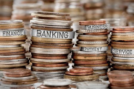 Photo of various stacks and rows of coins isolated on white with BANKING concept related words imprinted on metal surface