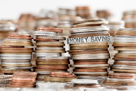 Photo of various stacks and rows of coins isolated on white with MONEY SAVING concept related words imprinted on metal surface