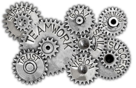 Macro photo of tooth wheels with TEAMWORK concept related words and icons imprinted on metal surface isolated on white