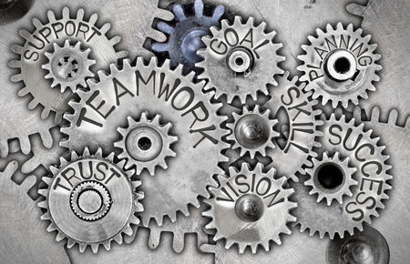 Macro photo of tooth wheels with TEAMWORK concept related words and icons imprinted on metal surface
