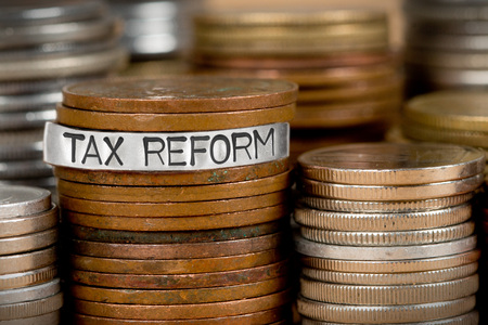 Photo of various stacks and rows of coins with TAX REFORM concept word imprinted on metal surface Stock Photo
