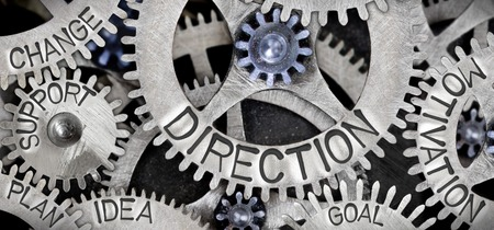 Macro photo of tooth wheel mechanism with DIRECTION concept related words and icons imprinted on metal surface