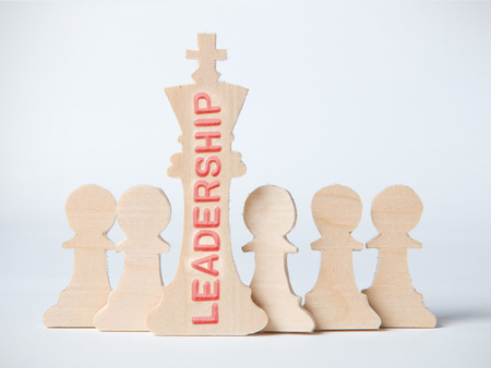 Chess figures, king and pawns with LEADERSHIP concept word imprinted on wooden surface