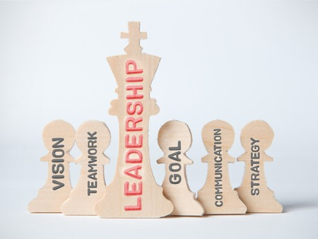 Chess figures, king and pawns with LEADERSHIP concept related words imprinted on wooden surface Stock Photo