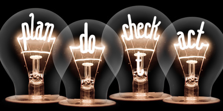 Photo of light bulb group with shining fibers in PLAN, DO, CHECK and ACT shape isolated on black background; concept of Business Process, Four Step Management