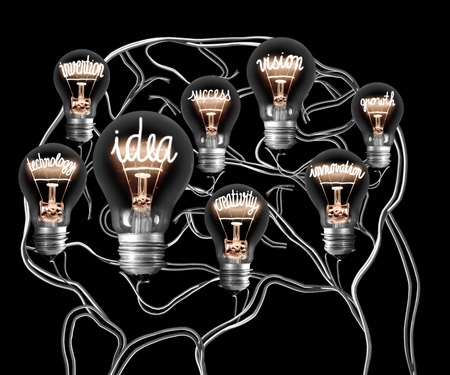 Photo of light bulb with shining fibre in a shape of IDEA, INNOVATION and CREATIVITY concept related words inside a brain made of wires isolated on black background
