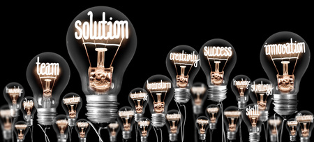 Light bulbs group with shining fibers in a shape of SOLUTION and INNOVATION concept related words isolated on black background