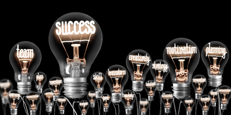Large group of light bulbs with shining fibers in a shape of Success and Motivation concept related words isolated on black background 스톡 콘텐츠