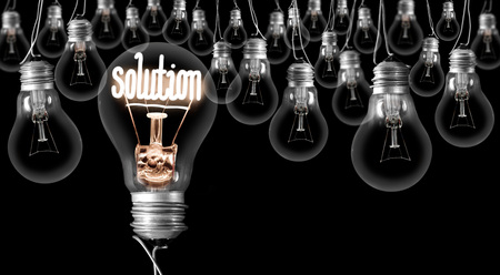 Group of dimmed light bulbs with one of them shining, concept of Solution, isolated on black background