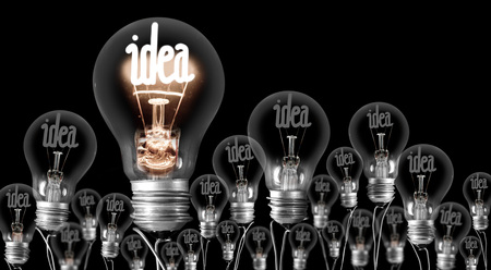 Large group of shining and dimmed light bulbs with fibers in a shape of Idea concept words isolated on black background
