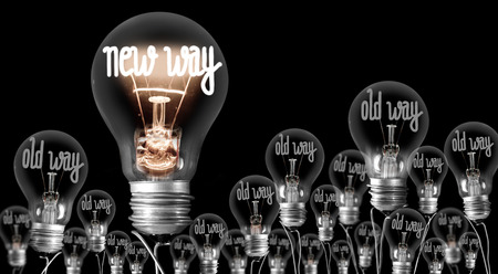 Large group of shining and dimmed light bulbs with fibers in a shape of New and Old Way words isolated on black background; concept of Innovation, Development and Success